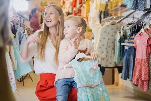 young mother with her little daughter having fun in the children's clothing store