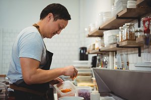 Chef adding chopped carrot into bowl in commercial kitchen