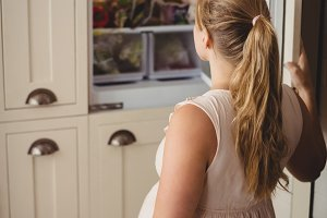 Pregnant woman looking for food in refrigerator in kitchen