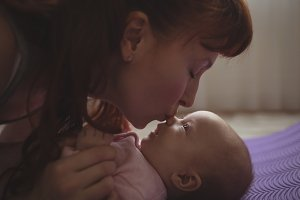 Loving mother kissing on baby nose at home