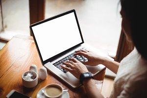 Woman using laptop in café