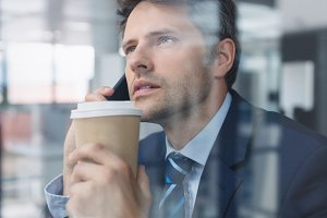 Businessman using mobile phone and holding disposable coffee cup