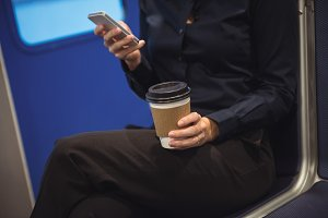 Businesswoman with coffee cup using phone while sitting in train