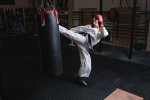 Woman practicing karate with punching bag