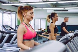 Woman training over treadmill on fitness center