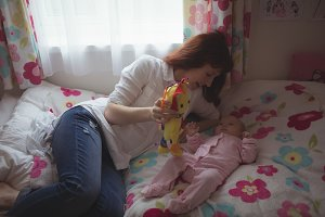 Mother showing toy to baby in bed