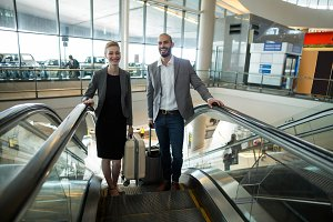 Smiling businesspeople with luggage going up on escalator