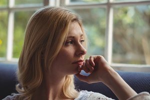 Thoughtful woman looking through window in living room