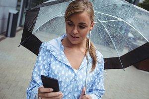 Beautiful woman holding umbrella while using mobile phone