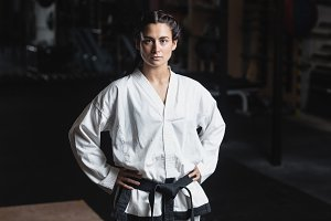 Portrait of karate woman standing with hand on hip