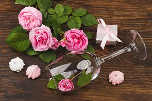 Light pink roses in the wine glass and present box on the wooden background