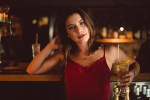 Portrait of beautiful woman holding cocktail glass at counter