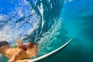 Surfer girl dive underwater