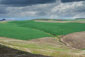 Rolling farm fields with storm