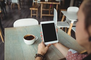 Woman using digital tablet while having cup of coffee