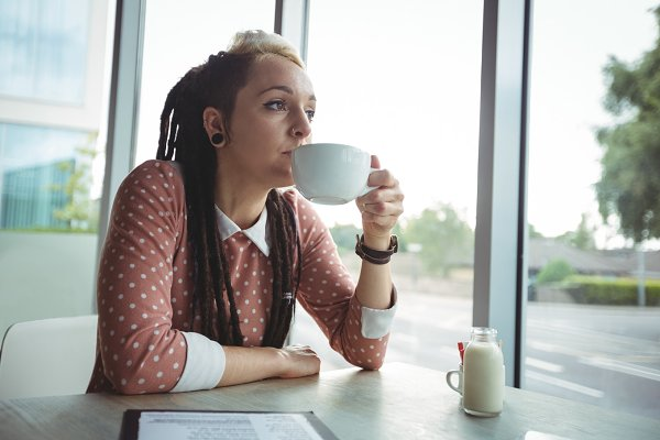 Thoughtful woman having cup of coff…