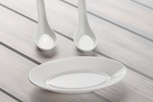 Spoons and ceramic dish to serve food. Crockery.