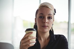 Portrait of woman holding disposable coffee cup