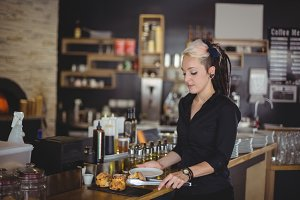 Waitress serving muffin in a plate at counter