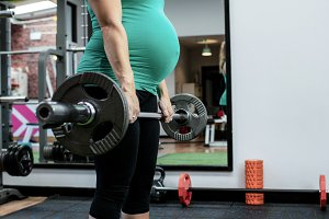Pregnant woman working out with barbell
