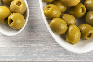 Stuffed olives on ceramic containers on wooden table. Copy space.