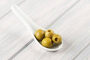 Stuffed olives on ceramic spoon on wooden table. Food.