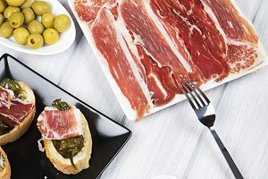 Ham topped with fried green peppers on black plate next to Iberian ham. Spanish gastronomy. Vertical shoot.