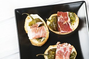 Ham slices with fried green peppers on black plate. Spanish gastronomy. Food.