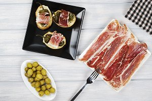Top view of Iberian ham, ham tops with stuffed peppers and olives next to a bottle of beer. Horizontal shoot.