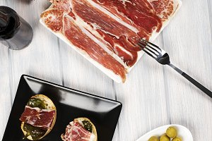 Top view of Iberian ham, ham tops with stuffed peppers and olives next to a bottle of beer. Vertical shoot.