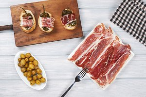 Top view of a plate of Iberian ham and ham tops with fried green peppers on white wooden board. Spanish gastronomy.
