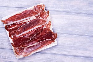 Top view of a plate of Iberian ham on white wooden board. Spanish gastronomy. Copy space.
