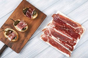 Top view of Spanish tapas of ham and green pepper, and a plate of Iberian ham on white wooden board. Spanish gastronomy.