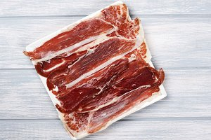Top view of a plate of Iberian ham on white wooden board. Spanish gastronomy.