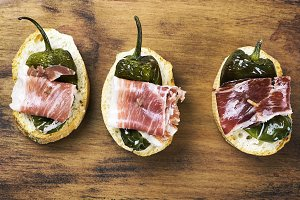 Top view of Spanish tapas of ham and green peppe on wooden board. Spanish gastronomy. Food.