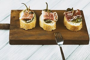 Spanish tapas of ham and green pepper next to a fork on wooden board. Spanish gastronomy. Food.