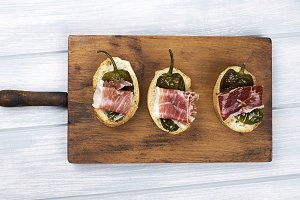 Top view of Spanish tapas of ham and green pepper on white wooden board. Spanish gastronomy.