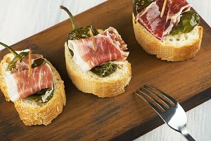 Close-up of Spanish tapas of ham and green pepper next to a fork on wooden board. Spanish gastronomy. Food.