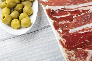 Close-up of a plate of ham and olives on wooden table. Spanish typical food. Copy space.