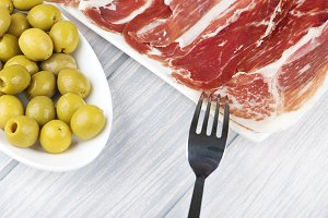 Close-up of a plate of ham and olives on wooden table. Spanish typical food.