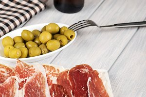 Close-up of olives, ham and beer next to a napkin on wooden table. Food. Vertical shoot.