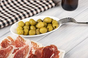 Close-up of olives, ham and beer next to a napkin on wooden table. Food