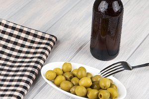 Bottle of beer and olives next to a napkin on wooden table. Alcohol.