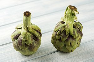 Artichokes on white wooden table.