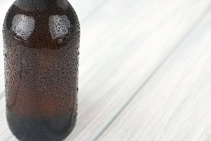 Close-up of beer bottle on wooden table. Alcohol.