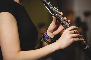 Mid-section of female student playing clarinet