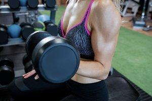 Woman lifting dumbbells at gym