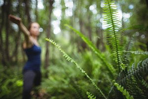 Blurred woman performing yoga in forest