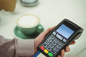 Hands making payment through credit card in cafe