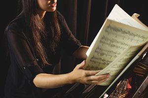 Female student looking at sheet music while playing a piano